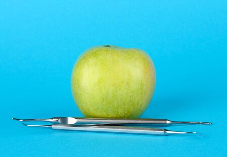 Green apple and dental tools on color background Stock Photo - 17133123