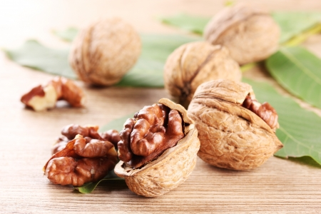 walnuts with green leaves, on wooden background Stock Photo - 17138257