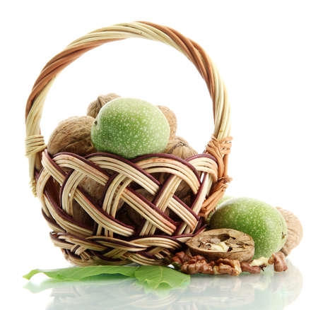 walnuts with green leaves in basket, isolated on white photo