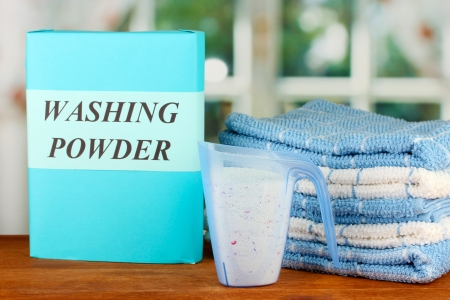 Box of washing powder with blue measuring cup and towels, on wooden table close-up photo