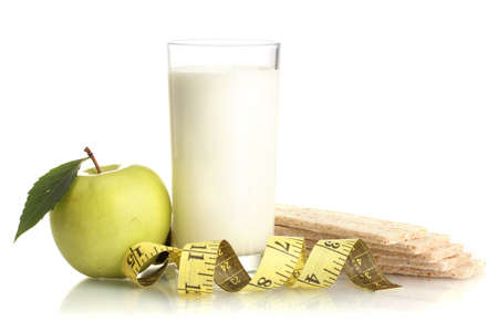 Glass of kefir, green apple, crispbreads and measuring tape isolated on white photo