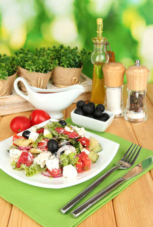 Fresh greek salad on plate on wooden table on natural background photo