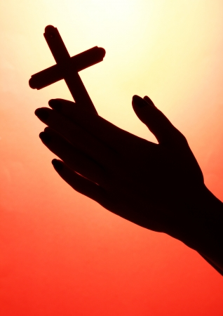 female hands with crucifix, on red background photo
