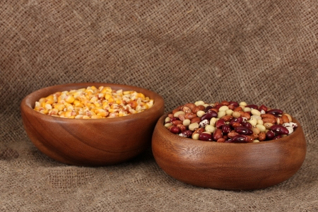 Raw corn, and beans in wooden bowls on table on sackcloth  background photo
