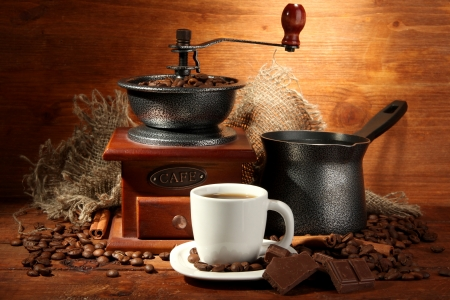 turkish coffee: Coffee grinder, turk and cup of coffee on brown wooden background Stock Photo