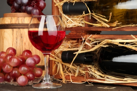 Wooden case with wine bottles, barrel, wineglass and grape on wooden table on grey background Stock Photo - 17138285