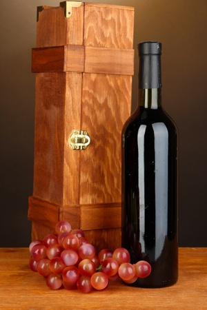 dura: Wooden case with wine bottle on wooden table on brown background