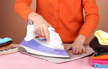 Young woman ironing her clothes, on brown background Stock Photo - 17138229