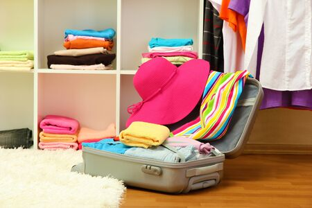 Open silver suitcase with clothing in room Stock Photo - 17138305