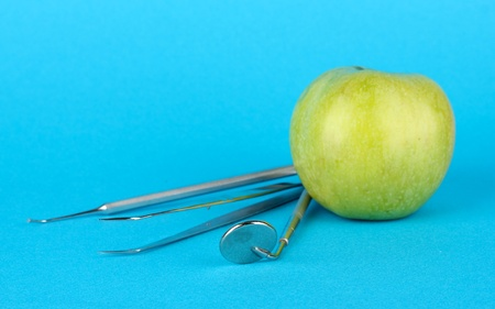 Green apple and dental tools on color background Stock Photo - 17138167