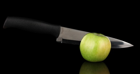 Green apple and knife isolated on black Stock Photo