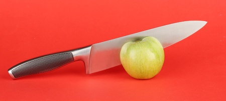 Green apple and knife on red background Stock Photo - 17138026