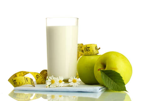 Glass of kefir, green apples and measuring tape isolated on white photo