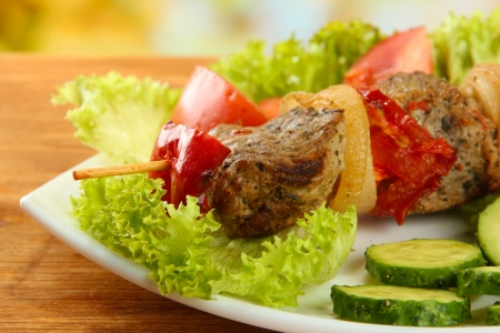 tasty grilled meat and vegetables on skewer on plate, on wooden table Stock Photo - 17139083