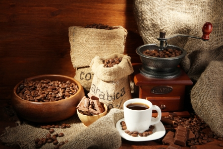 turkish coffee: Coffee grinder and cup of coffee on brown wooden background