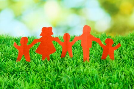 Paper people on green grass on bright background Stock Photo - 17139285