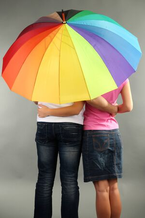 Loving couple with umbrella on grey background photo