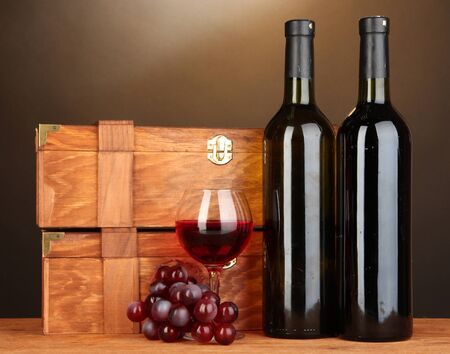 cabarnet: Wooden cases with wine bottles on wooden table on brown background Stock Photo