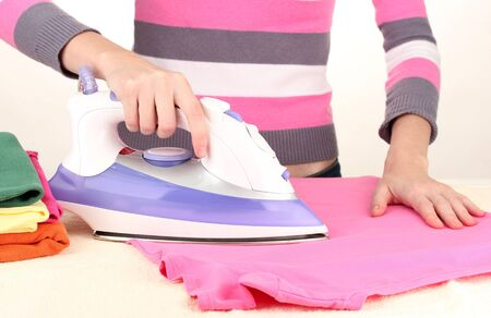 Young woman ironing her clothes, isolated on white Stock Photo - 17138818