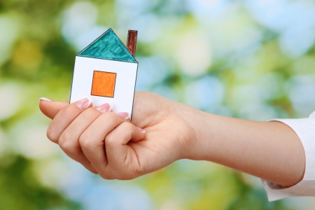 concept: woman hand with paper house on green background, close up Stock Photo - 17188560