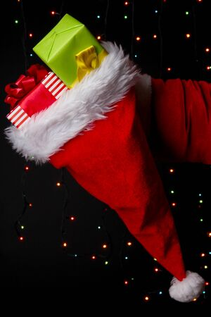 Santa Claus hand holding gifts on bright background photo
