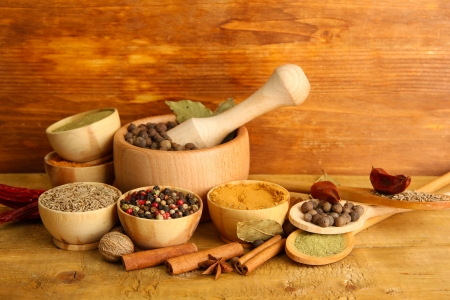 mortar, bowls and spoons with spices, on wooden background photo
