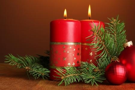 velas de navidad: Dos velas y decoraciones de la Navidad, sobre fondo marr?n