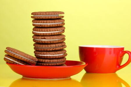 Chocolate cookies with creamy layer on red plate yellow background Stock Photo - 17187715