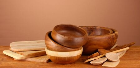 Wooden kitchen utensils on table on brown background photo
