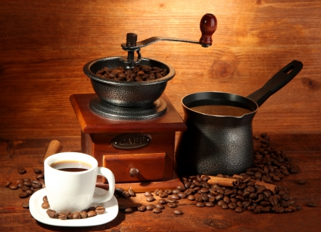 Coffee grinder, turk and cup of coffee on brown wooden background photo