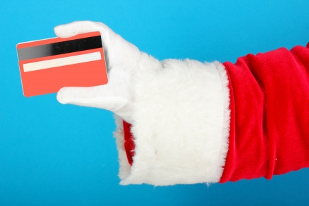 christmas debt: Santa Claus hand holding red credit card on blue background