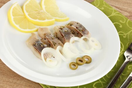 Dish of herring and lemon on plate on wooden table close-up photo
