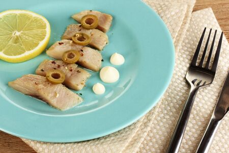 Dish of herring and lemon on plate on wooden table close-up Stock Photo - 17189081