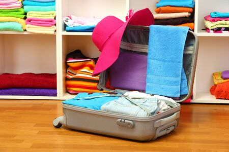 Open silver suitcase with clothing in room photo