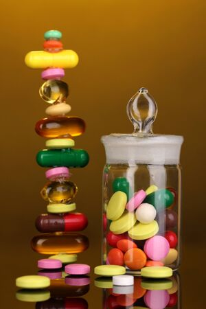 receptacle: Capsules and pills hill and in receptacle on yellow background