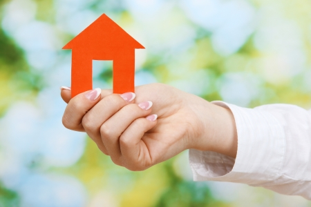 concept: woman hand with paper house on green background, close up photo