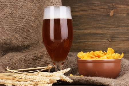 Glass of beer with plate of chips on wooden table on sacking background photo