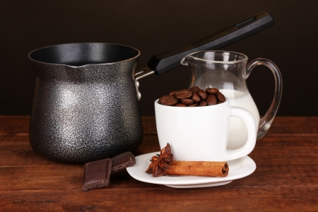 Coffee maker with milk and white cup on wooden table photo
