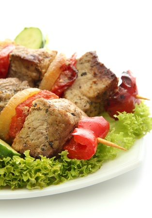 tasty grilled meat and vegetables on skewers on plate, isoalted on white photo