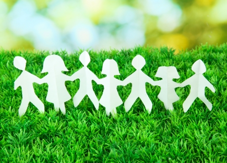 friends and family: Paper people on green grass on bright background