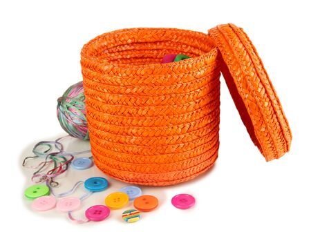 Orange wicker basket with accessories for needlework isolated on white photo
