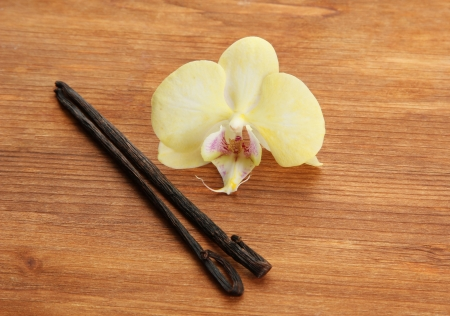 Vanilla pods with flower, on brown wooden background photo