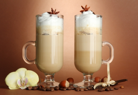 Fragrant coffee latte in glasses cups with spices, on brown background photo