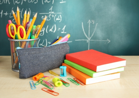 Back to school - blackboard with pencil-box and school equipment on table photo