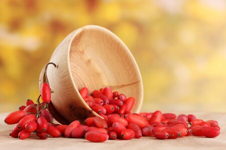 ripe barberries in wooden bowl, on table, on yellow background photo
