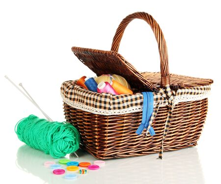 Wicker basket with accessories for needlework isolated on white photo