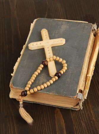 Bible, rosary and cross on wooden table close-up Stock Photo - 17246010