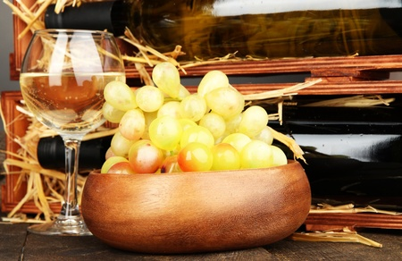 Wooden case with wine bottles, wineglass and grape close up Stock Photo - 17245995