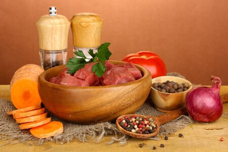 microelements: Raw beef meat marinated with herbs and spices on wooden table on brown background