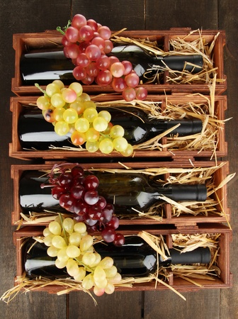 Wooden case with wine bottles on wooden table photo